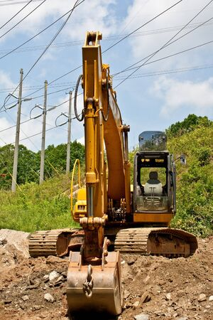 front end loader: A front end loader on a hill under high power lines Stock Photo