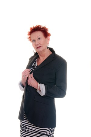 lapels: An older woman with red hair wearing a black jacket holding lapels