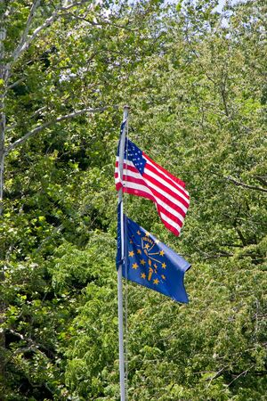 A flagpole in a park with an American and Indiana flag