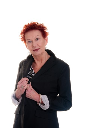lapels: An older woman with wild red hair holding lapels of a black jacket
