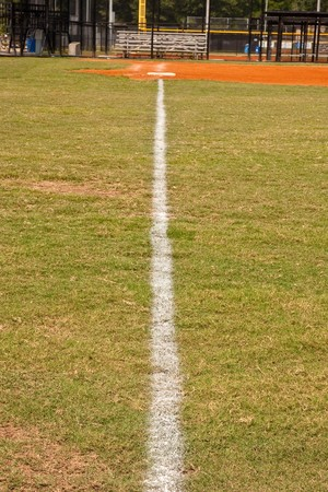 foul: A white chalk foul line down the first base line of a baseball field Stock Photo