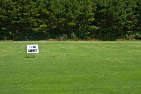 fescue: A new field of grass with a field closed sign on it.