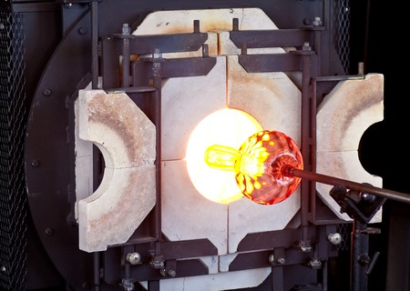 glassblower: A glass blower turning a vase on a rod in a hot oven