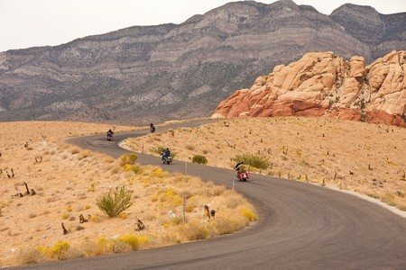 Motorcyclists riding a road into the dessert mountains photo