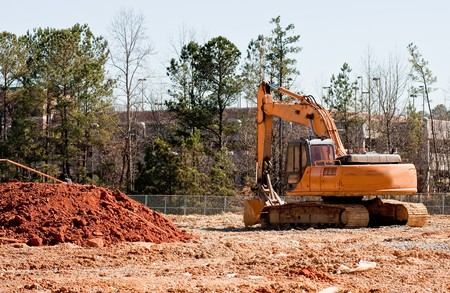 earth moving: A large yellow earth moving machine by pile of dirt at site