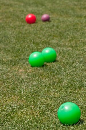 Green, red, and purple bocce balls on lawn Stock Photo - 8153671