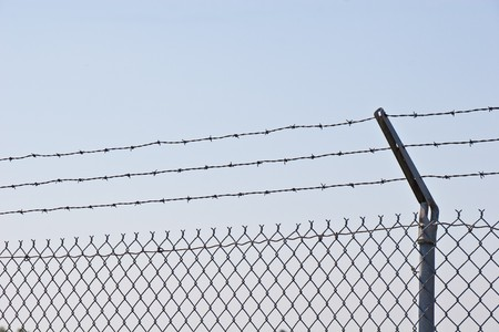 barbed wire fence: A chain link fence topped with three strands of barbed wire