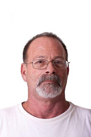 회색 수염과 콧수염이있는 나이 든 남자가 심각한 안경을 쓰고있다.