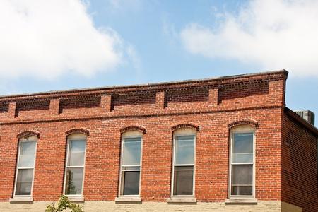 좋은 하늘 아래 나무 샷시 창문이있는 오래된 벽돌 건물