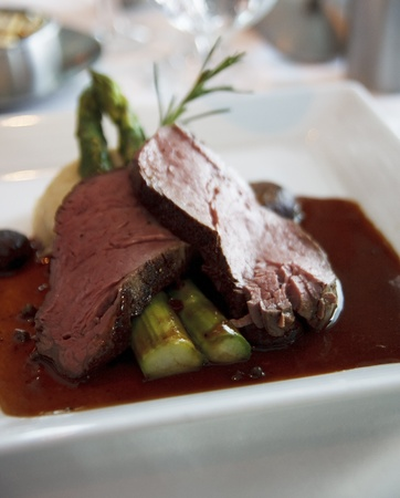 jus: Slices of rare roast beef on asparagus spears with au jus and a rosemary sprig
