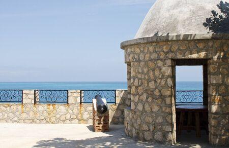 Cañón de hierro por un muro de piedra y el edificio pretende mar Foto de archivo - 8802514