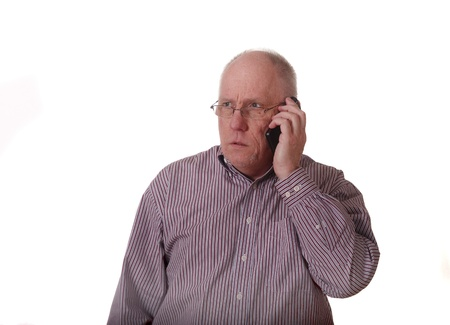 An older balding guy in a striped shirt on a smart phone looking upset photo