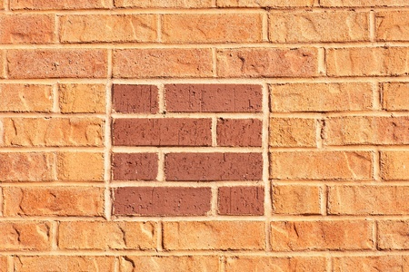 An orange brick wall with a red brick square Stock Photo - 9133595