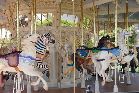 A carousel in a children's park with horses and zebras
