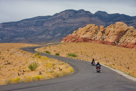 curving: Motorcyclists riding along a curving road in the desert toward distant mountains Stock Photo