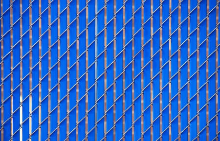 A chain link fence with blue metal slats for privacy Stock Photo
