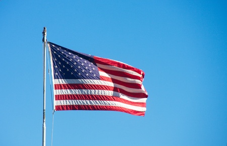 An American flag blowing in the wind against a clear blue sky Фото со стока