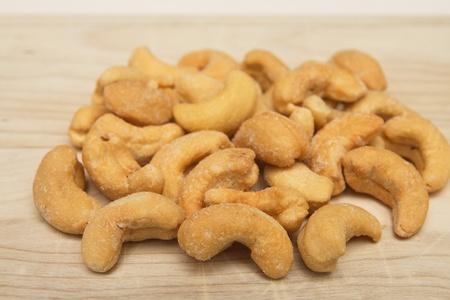 Salted cashews on a wood cutting board Фото со стока
