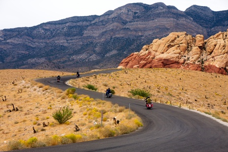Motorcycles on a Winding Desert Road Toward the Mountains