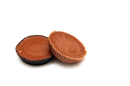 Two chocolate covered peanut butter candies on a white background
