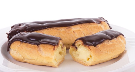 eclair: A whole eclair and a cut eclair on a white plate Stock Photo