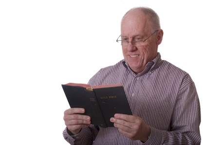 An older balding man wearing a striped shirt and glasses reading the bible and smiling photo