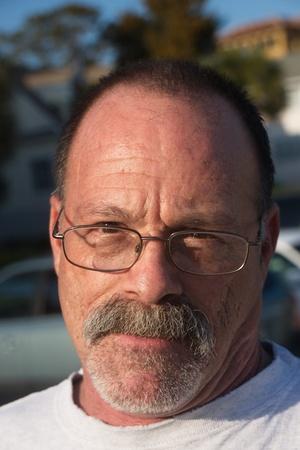夕日の光の中で年上のはげかかった男灰色のひげと口ひげを着てメガネします。 写真素材