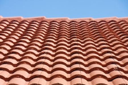 shingles: Filas de tejas rojas bajo un cielo azul claro