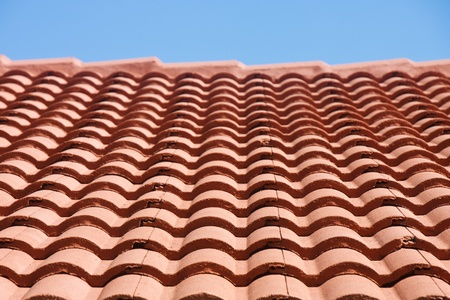 Rows of red roof tiles under a clear blue sky Archivio Fotografico