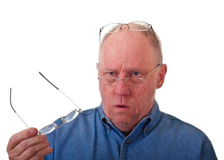 An older balding man in blue denim shirt with three pairs of reading glasses photo