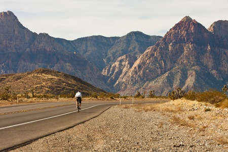 A lone cyclist peddling up a desert highway toward distance mountains photo