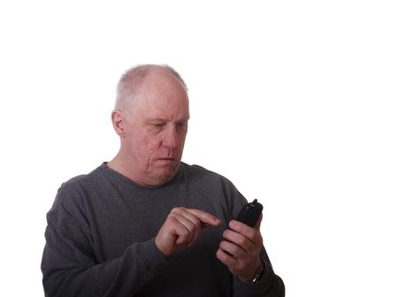 An older balding man looking worried while trying to dial a telephone