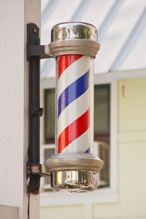 A classic red, white and blue barber pole on a wood post Imagens