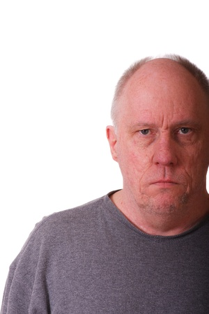 An older balding man in gray shirt looking grumpy or mad photo