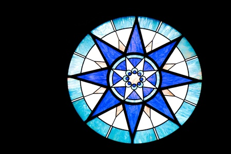 A round blue and white stained glass window on black background Фото со стока