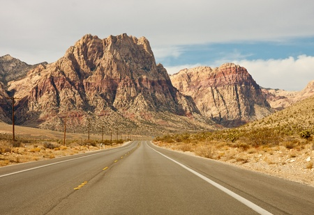 A wide empty road in the desert toward distant mountains photo
