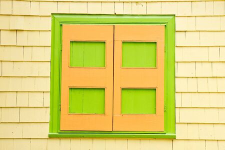 Bright green and orange shutters on a yellow siding house photo