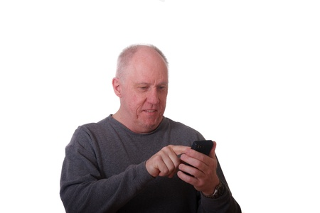 An older balding man using a smart phone and smiling photo