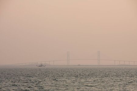 shrimp boat: A shrimp boat near a suspension bridge at dusk through fog