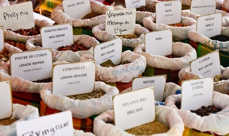 Many labeled spices in an outdoor market photo