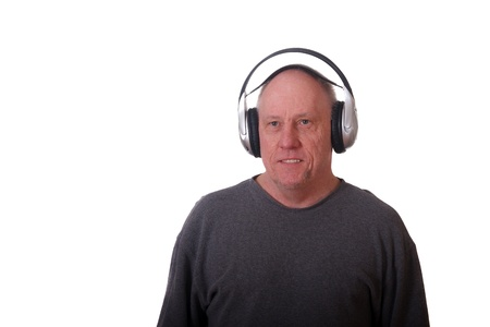 An older balding man in a grey shirt wearing wireless headphones and smiling