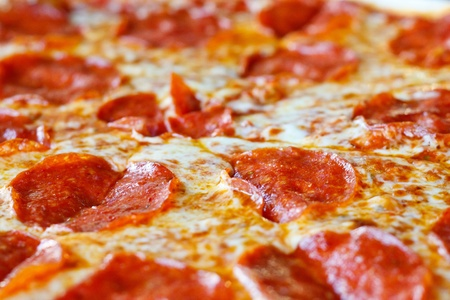 topping: A hot, cheesy, pepperoni pizza sliced and ready to eat Stock Photo