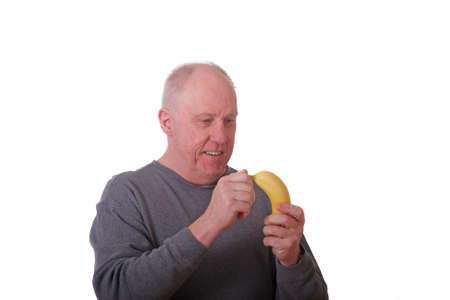 An older balding man in a grey shirt about to peel a fresh yellow banana Stock Photo - 10589160