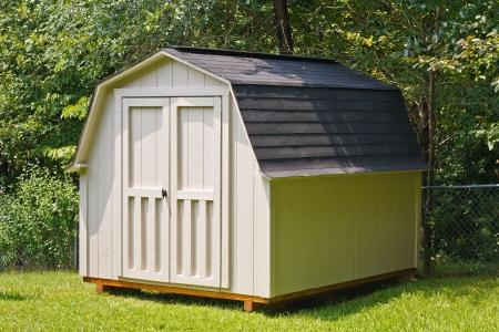 A wood utility shed in a back yard Foto de archivo