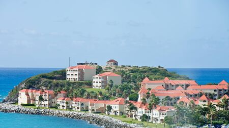 A tropical peninsula covered with stucco mansions with red tile roofs photo