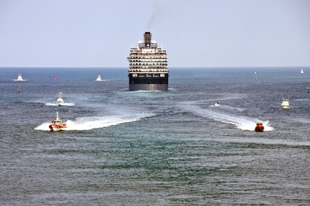 guar: Two Coast Guar Boats Speeding away from a large blue and white cruise ship