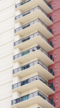 A column of condo balconies by a red stucco wall photo