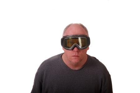 An older man looking through yellow ski goggles photo
