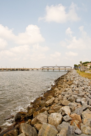 dike: A rock sea wall leading toward a traditional pier Stock Photo