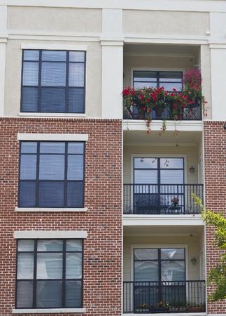 Bloemen groeien op balkons van baksteen en stucwerk condos Stockfoto